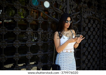 Trendy woman searching number on mobile phone while standing outdoors in summer day, young female dressed in stylish clothes reading text message on cell telephone before meeting with boyfriend  - stock photo