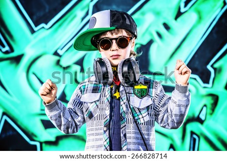 Trendy 7 year old boy on the street. Graffiti background. Modern generation. - stock photo