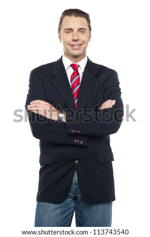 Trendy young business in casual attire posing with folded arms