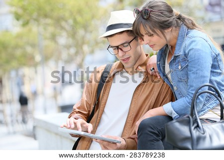 Trendy young couple connected on tablet and smartphone in town - stock photo