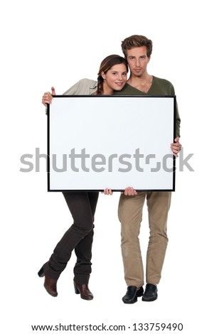 Trendy young couple stood with blank frame - stock photo