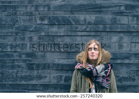 Trendy young female student in warm winter fashion standing thinking or daydreaming leaning against a textured grey wall looking up towards copy space above her head and to the left of the frame - stock photo