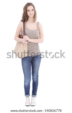 Trendy young female student wearing jeans and a pretty summer top and carrying a large cloth bag over her shoulder, full length portrait on white