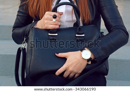 Trendy young girl in black leather jacket holding big black handbag street background .  Fashion accessories - stock photo