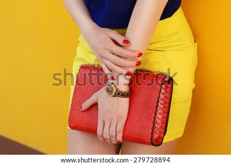 Trendy young girl in yellow short skirt and blue blouse holding red leather handbag . Outdoor shot  - stock photo