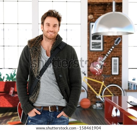 Trendy young man at home, smiling.