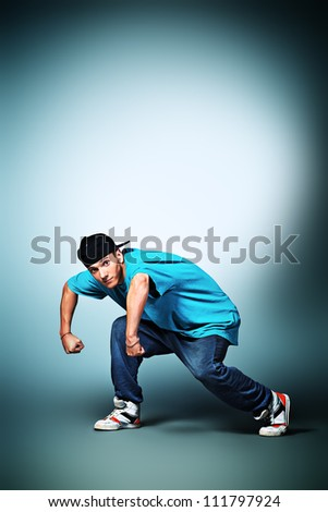 Trendy young man dancing hip-hop at studio.
