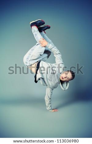 Trendy young man dancing hip-hop at studio. - stock photo