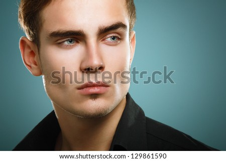 Trendy young man in black shirt, portrait of sexy fashion boy looking right over dark blue background - stock photo