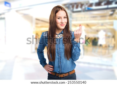 Trendy young woman doing the money gesture. Over shopping center background - stock photo