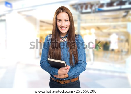 Trendy young woman holding a black book. Over shopping center background
