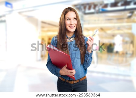 Trendy young woman holding a red folder and a pen. Over shopping centre background