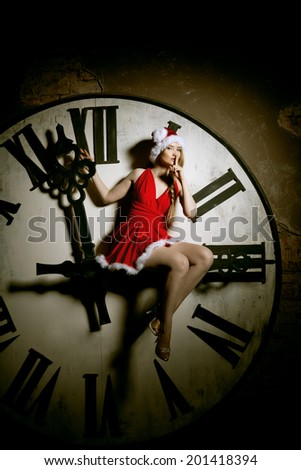 Trendy young woman in Santa costume on the big dial. Girl and clock in Christmas. New Year watch