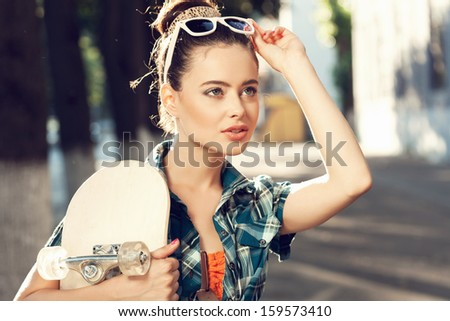 Trendy young woman in  summer dress with skateboard. Outdoors. Urban lifestyle shot. - stock photo