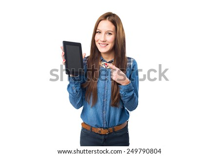Trendy young woman pointing with her finger to a tablet. Over white background