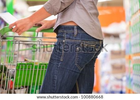 Trendy young woman shopping with trolley at supermarket - stock photo