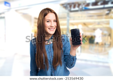 Trendy young woman showing a smart phone. Over shopping centre background - stock photo