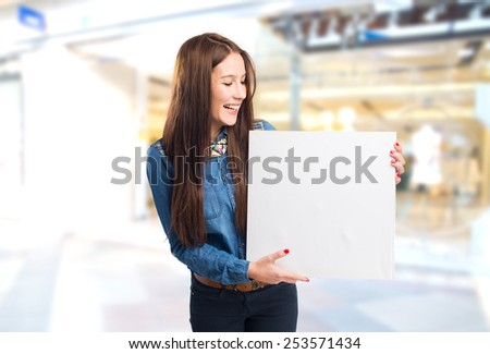 Trendy young woman showing a white canvas. Over shopping center background - stock photo