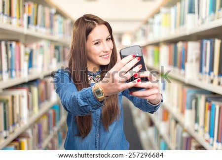 Trendy young woman taking a selfie with a smart phone. Over library background - stock photo