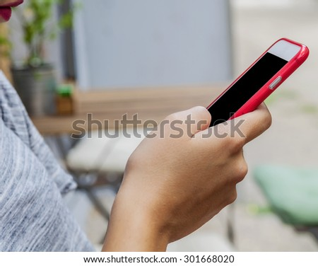 Trendy young woman use a smart phone in coffee shop - stock photo