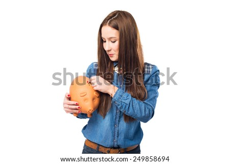 Trendy young woman using a piggy bank. Over white background - stock photo