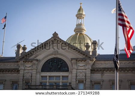 TRENTON, NJ - APRIL 4, 2015: The American Flag flying in front of the New Jersey State House located in Trenton. The capitol building for the state of New Jersey is located on State St. - stock photo