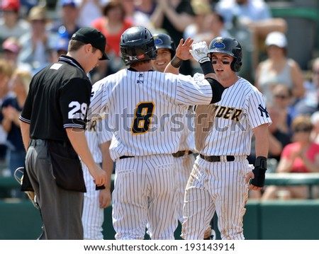 TRENTON, NJ - MAY 11: Teammates wait at the plate to congratulate Trenton Thunder outfielder Ben Gamel (8) after a homer during the Eastern League game May 11, 2014 in Trenton, NJ. - stock photo