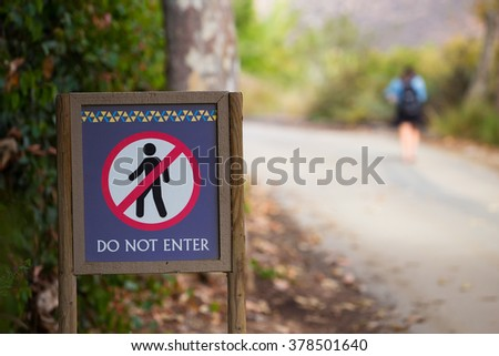 Trespassing person walking right past a sign that says Do Not Enter. - stock photo