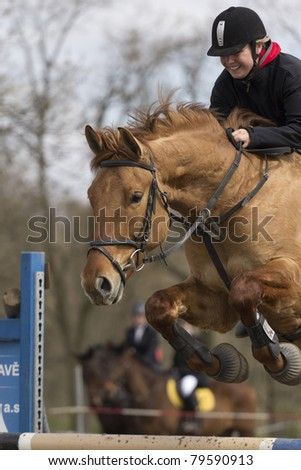 "TRESTINA - APRIL 09: Unidentified woman rider in action at ""Jump equestrian facilities"" on April 09, 2011 in Trestina (Czech Republic) - stock photo"