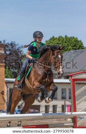 "TRESTINA, CZECH REPUBLIC - MAY 16: Young horsewoman in action at ""Equestrian Hobby Series 2015"" on May 16, 2015  in Trestina, Czech Republic."
