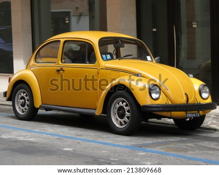 TREVISO, ITALY - CIRCA JULY 2014: Yellow Volkswagen Beetle vintage car parked in a street of the city centre.  - stock photo