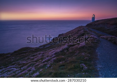 Trevose Head lighthouse on rocky cliffs in Cornwall, England at twilight - stock photo
