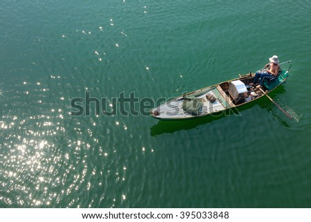 Tri An Lake, Dong Nai Province, Vietnam - March 6, 2016: A fisherman's boat on the lake in the early morning. This is a fisherman who lives in the fishing village of Tri An Lake