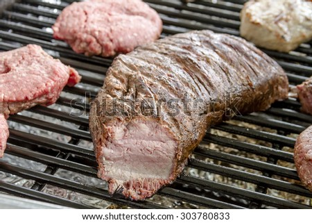 Tri-tip beef and hamburgers cooking on grill at summer picnic