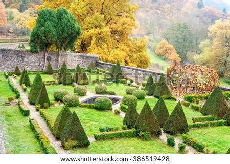 Triangle shaped topiary green trees in old ornamental garden of Burresheim Castle in autumn, Germany. Outdoors horizontal image - stock photo