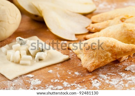Triangle wraps of puff pastry with blue cheese and pear. Baked, fresh and surrounded with raw ingredients - stock photo