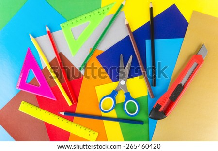 Triangles, ruler, scissors, pencils and cutter on background of colored paper - stock photo