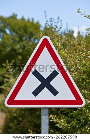 Triangular crossroads road sign on a country road junction - stock photo