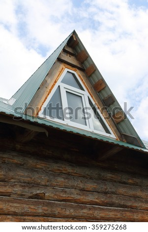 Triangular skylight of an attic of a village log house under construction against a cloudy sky