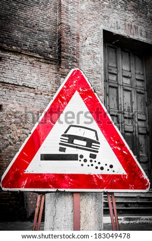 Triangular traffic warning sign propped up in front of an old brick building for damaged road edges or shoulders showing a car at a tilted angle - stock photo