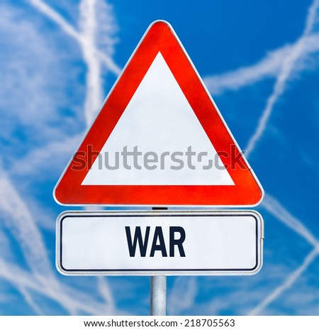 Triangular traffic warning sign with the word - War - against a blue sky criss-crossed by multiple white contrails from aircraft conceptual of a fight between enemy planes or anti aircraft missiles.