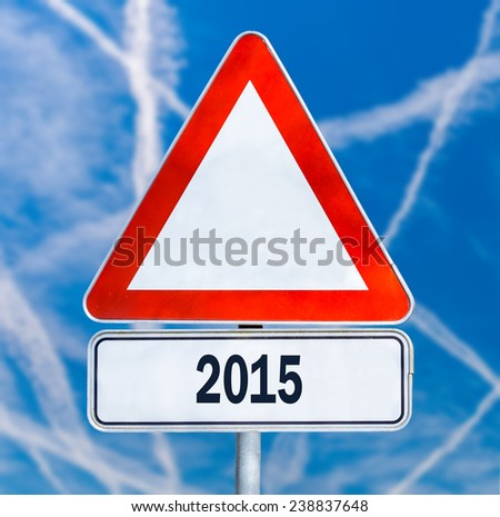 Triangular white traffic warning sign with the date 2015 over  blue sky with contrails. - stock photo