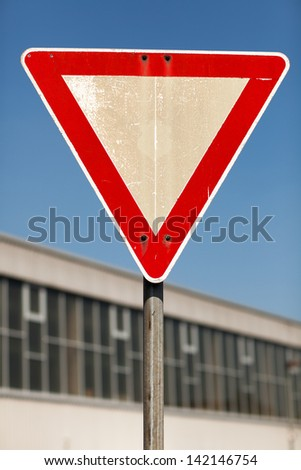Triangular yield traffic sign outside an urban building - stock photo