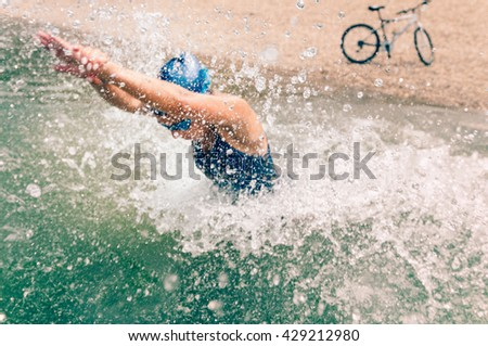 Triathlete in training, running into water. Focus set on water splash, athlete and bicycle blurred - stock photo