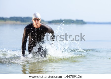 Triathlete running out of the water on triathlon race.