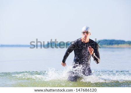 Triathlete running out of the water on triathlon race. - stock photo