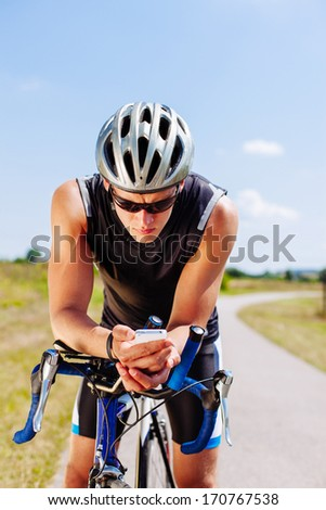 Triathlon cyclist navigating on his smartphone - stock photo