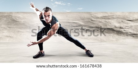 Triathlon runner man outdoor in urban concrete environment. Extreme fitness sport. Standing in stretch position. Warming up.