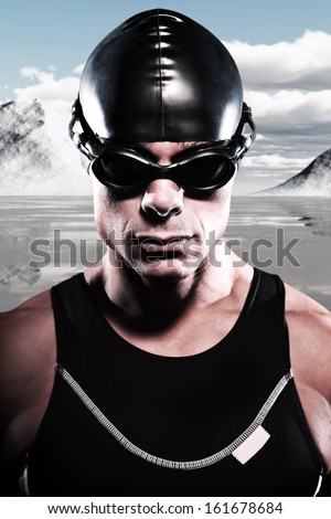 Triathlon swimmer man with cap and glasses outdoor at a frozen lake with snow mountains and blue cloudy sky. Extreme fitness sport. Close-up portrait.