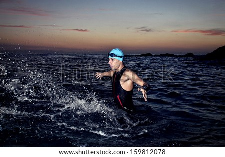 triathlon young athlete out of the sea at dawn - stock photo